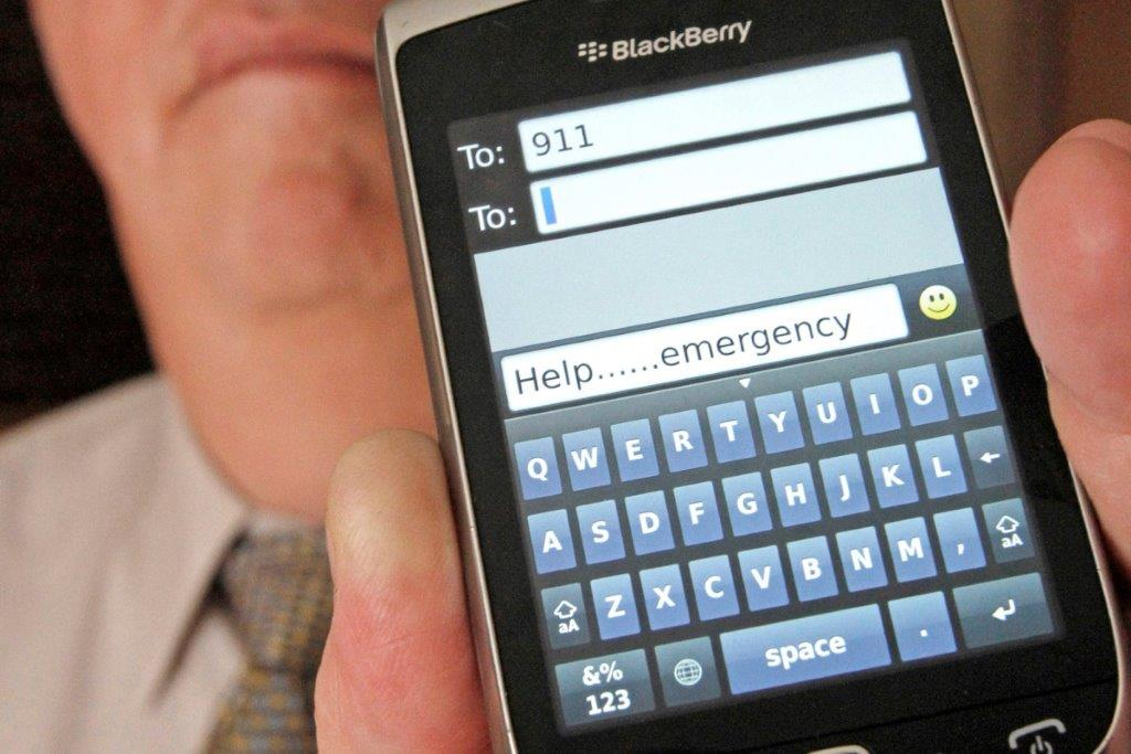 Man holding phone with an emergency text message for 911