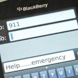 Person holding cell phone with 911 and emergency text message on the screen