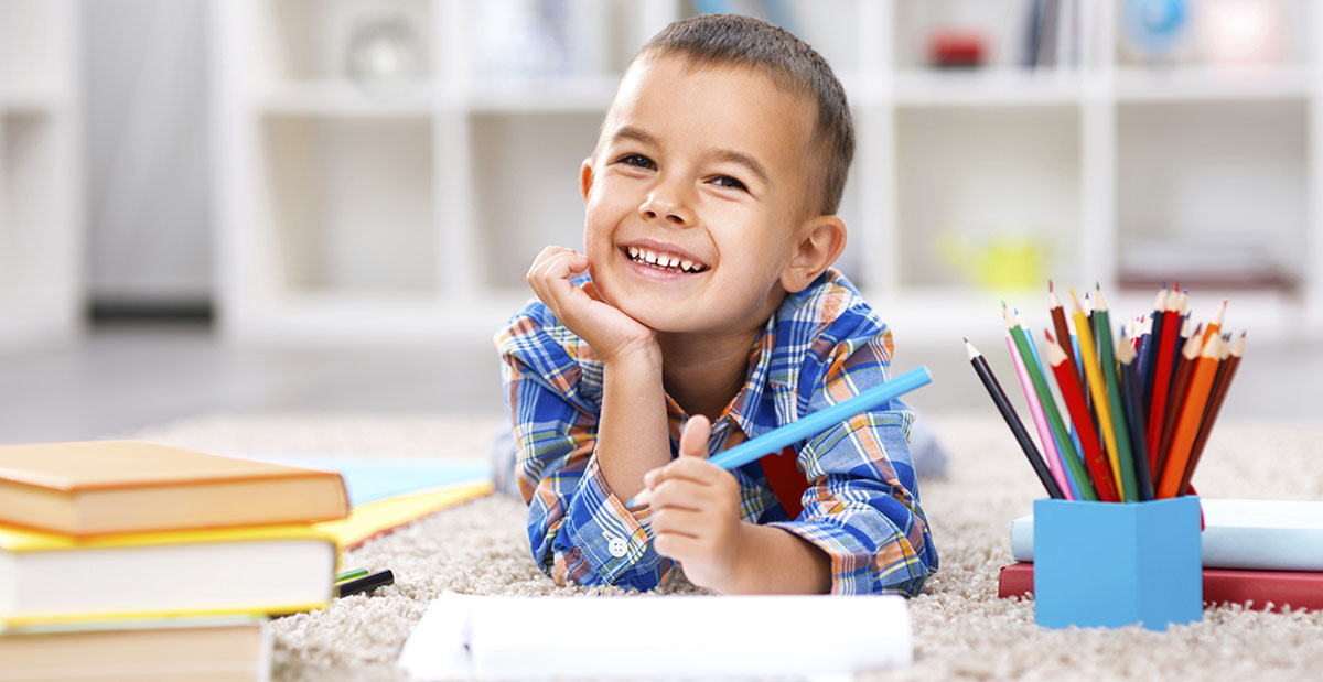 Smiling child in classroom holding pencil